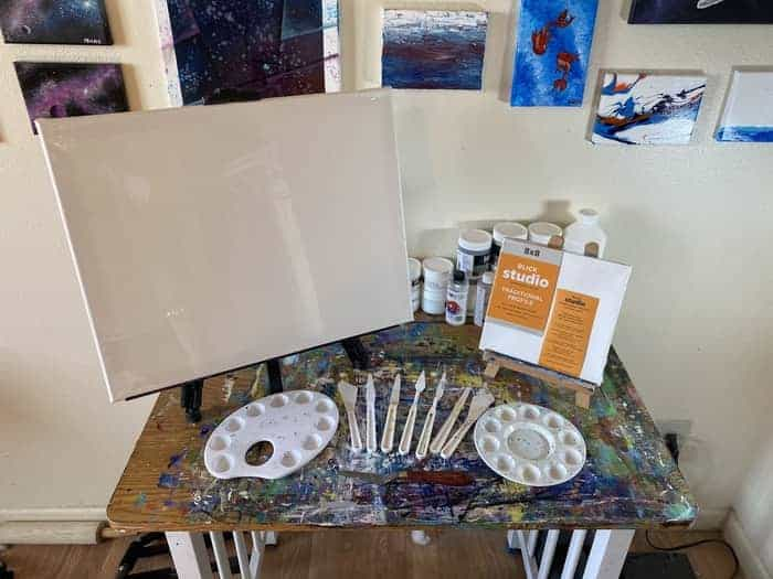 A large and small easel each holding a canvas behind a set of palette knives fanned out. There are also two different types of palettes on either side of the fanned out palette knives.
