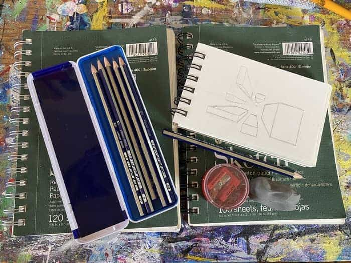Two sketch pads laid side by side. On top of the sketch pads are a pencil set, a clay eraser, a pencil sharpener, and a smaller sketch pad that has a sketch on perspective displayed.