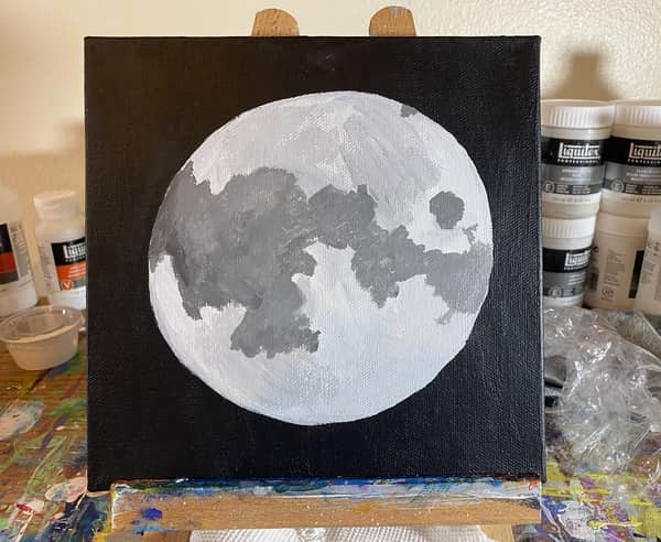 A gray circle with dark gray blotches on it.