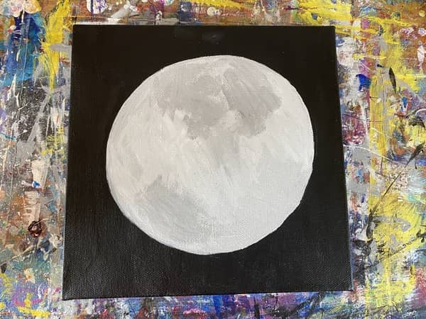 A black canvas with a light gray circle painted in the center of it.
